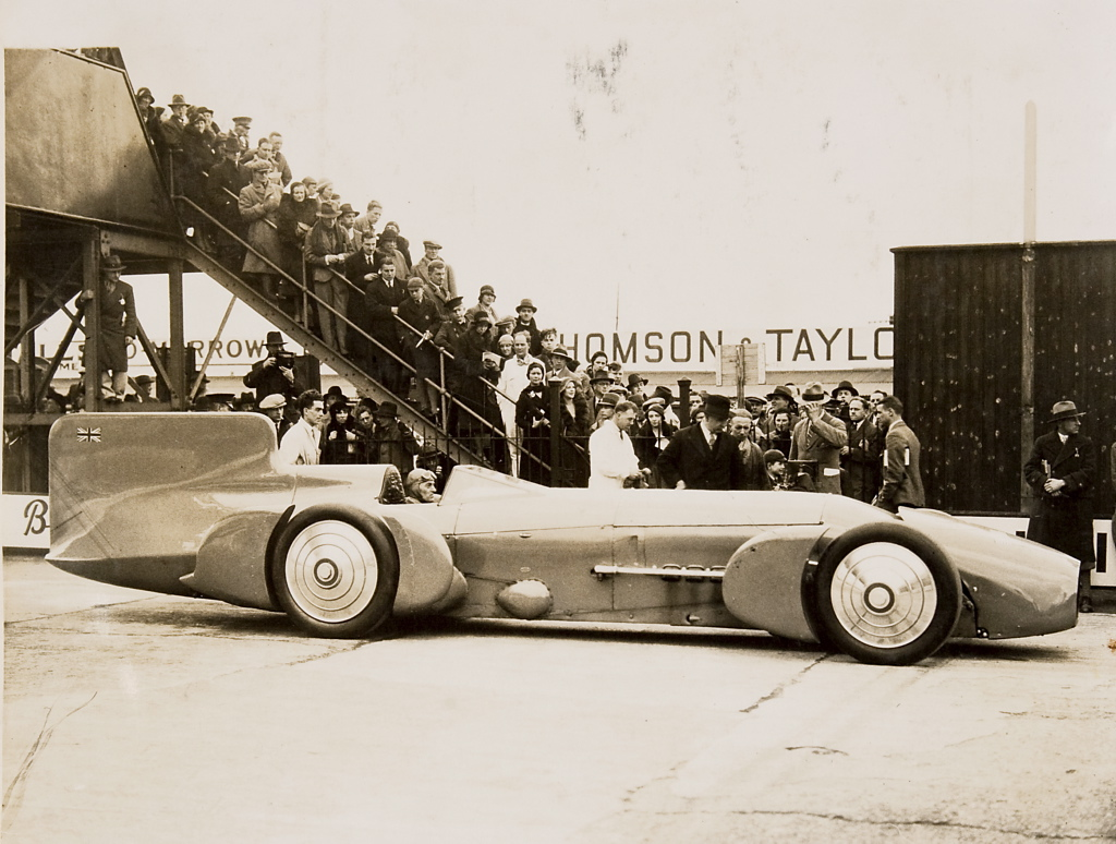 Sir malcolm campbell at the wheel of the bluebird with crowd 1926 1936